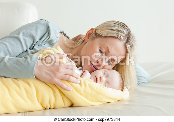 Mother relaxing next to her sleeping baby - csp7973344