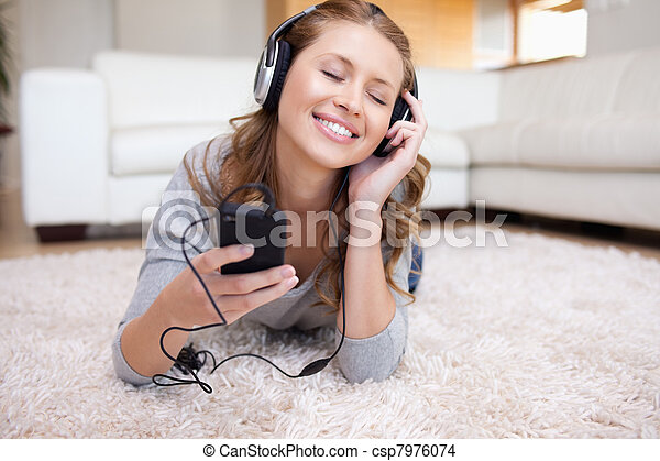 Young woman lying on the carpet listening to music - csp7976074