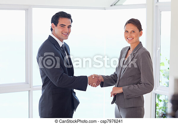 Side view of smiling trade partner shaking hands - csp7976241