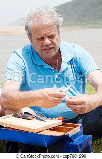 senior man putting bait on fishing hook - csp7981290