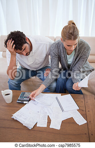 Portrait of a depressed couple doing their accounting - csp7985575