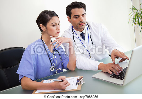 Young doctors working with a notebook - csp7986256