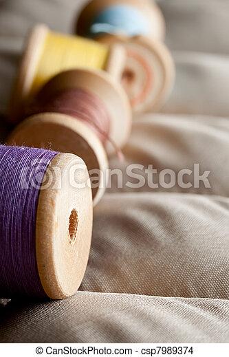 Thread bobbins on a gray fabric - csp7989374