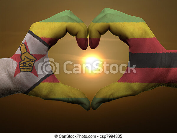 Gesture made by zimbabwe flag colored hands showing symbol of heart and love during sunrise - csp7994305
