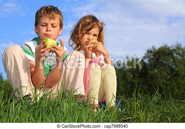 Two lovely children sit on a grass, against the blue sky and eat apples. - csp7998540