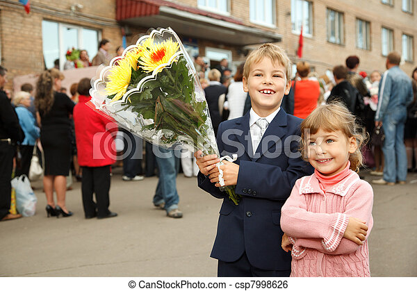 First class, brother and sister with  bouquet of flowers, standing at  entrance to school. - csp7998626