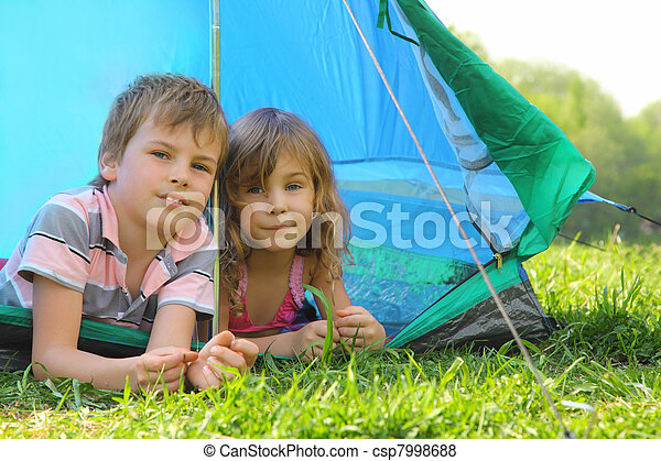 Little brother and sister lying inside blue tent on green grass on summer day and looking forward - csp7998688