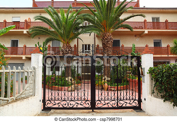 Forged black gate of sanatorium. palm trees and buildings of sanatorium can be seen outside gates  - csp7998701