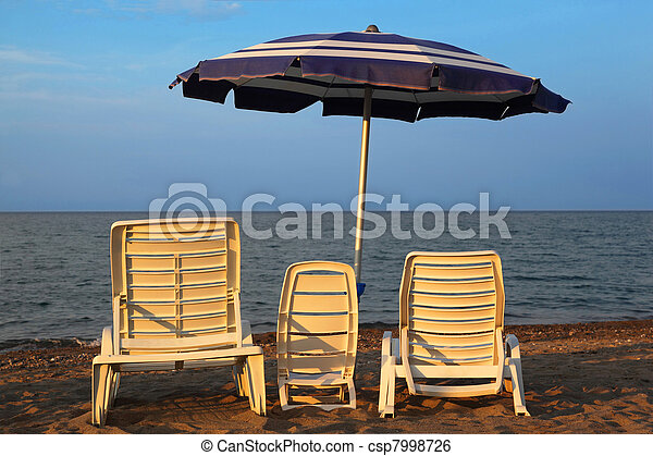 MANDATORICCIO, ITALY – JULE 20: Three lounge chairs on beach on Jule 20, 2010 in Mandatoriccio, Calabria, Italy. Calabria region visited annually by only 3% of Italy's 45 million tourists  - csp7998726