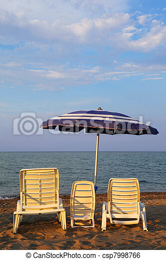 MANDATORICCIO, ITALY – JULE 20: Three lounge chairs for family on beach. Mother, father, child on Jule 20, 2010 in Mandatoriccio, Calabria, Italy. Calabria region visited annually by only 3% of Ital - csp7998766