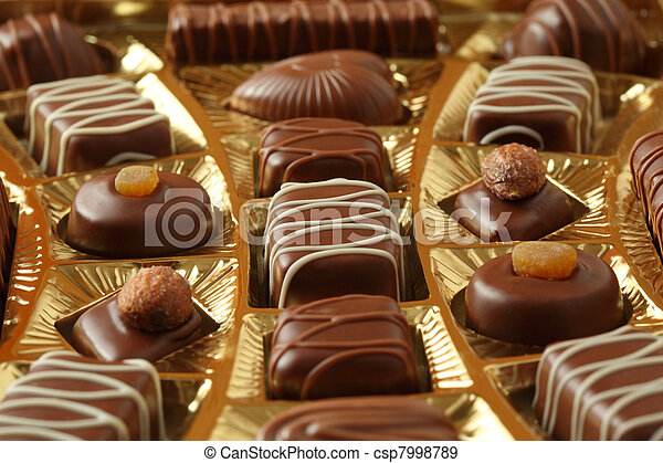 many chocolate appetizing candys with icing in golden box  - csp7998789