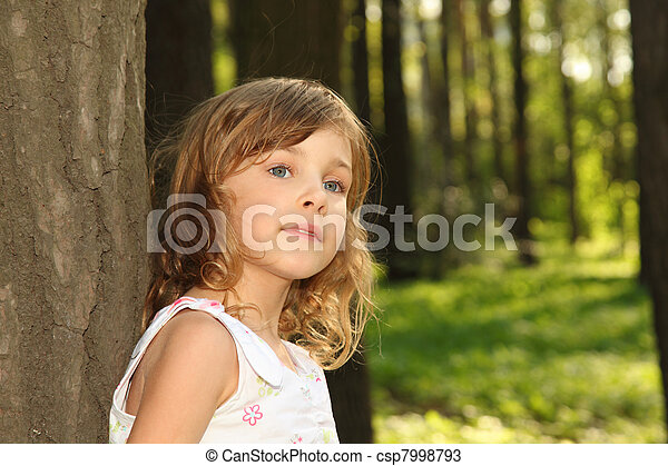 Little cute girl with curly blonde hair in white clothes leaning against a tree inside green forest at sunny day