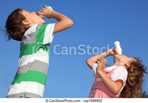 Small boy and the girl against the blue sky, with pleasure drink yoghurt. - csp7998802
