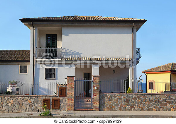 White two-storeyed cottage behind fence with  court and additional annexes near sea - csp7999439
