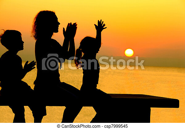 Mother with two children sits on  bench on  beach on sunset and merrily slam hands - csp7999545
