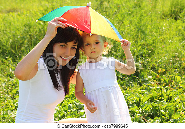 Mother and daughter hide under an umbrella from the sun - csp7999645