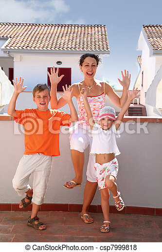 Mother with  girl and boy stand on  balcony on one leg and lift hands upwards and laugh - csp7999818
