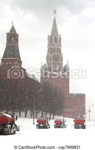 Column of snow-remover trucks on the road near Kremlin chiming clock of the Spasskaya Tower in Moscow, Russia at wintertime during snowfall - csp7999831