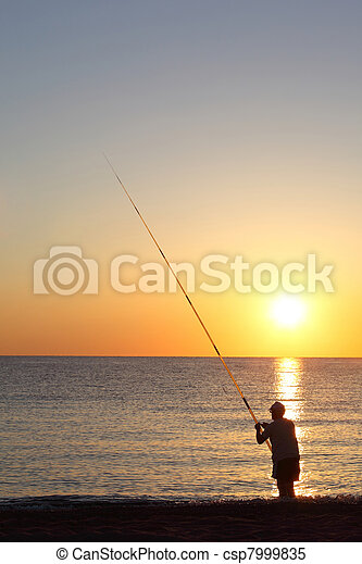 Fisherman stands ashore exterminating with  large fishing-rod and threads  bait - csp7999835