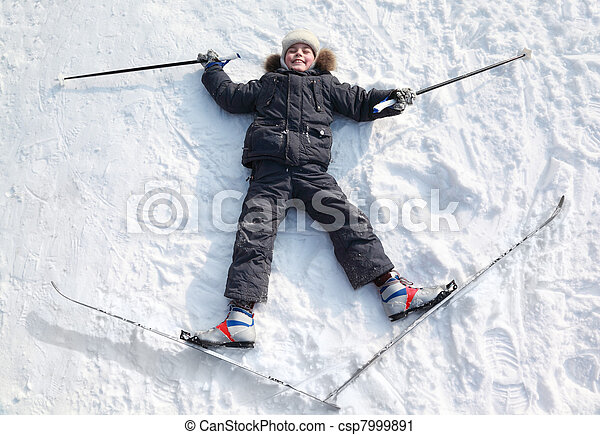 Young boy lying in cross-country skis and poles and stretching out arms and legs inside winter forest at sunny day - csp7999891
