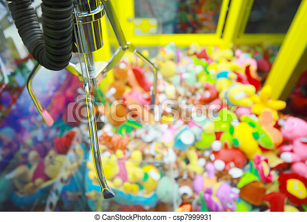 Capture device for soft toys on background of heap of colorful soft toys in arcade machine - csp7999931