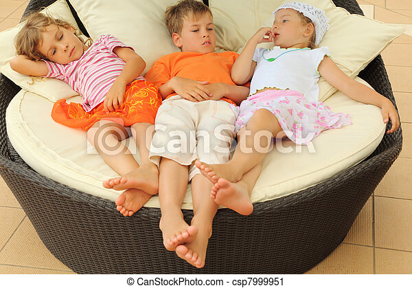 two tired little girls and boy lying on big circle armchair with pillows and having rest - csp7999951