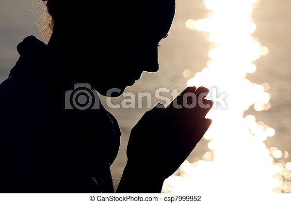 Silhouette of woman in  type, which sits ashore  and prays fold arms - csp7999952