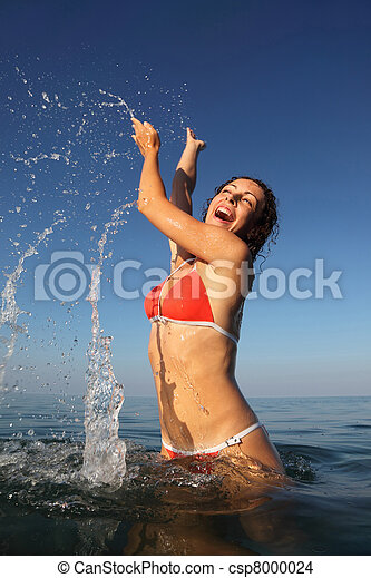 Young beautiful woman wearing red bathing suit spinning in sea. many drops - csp8000024