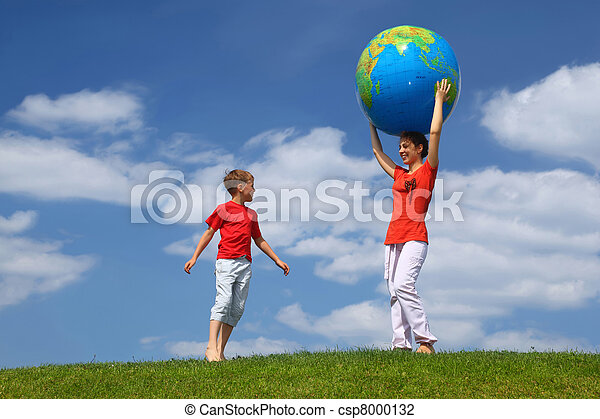 Mother stands on  grass and holds hands  large inflatable ball on  head,  boy comes running to it - csp8000132