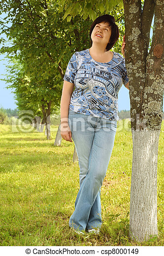 plumpy brunette woman standing on lawn near tree, smiling and looking at side, summer - csp8000149