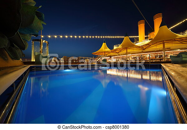 illuminated deck of ship at evening. swimming pool in center of image - csp8001380
