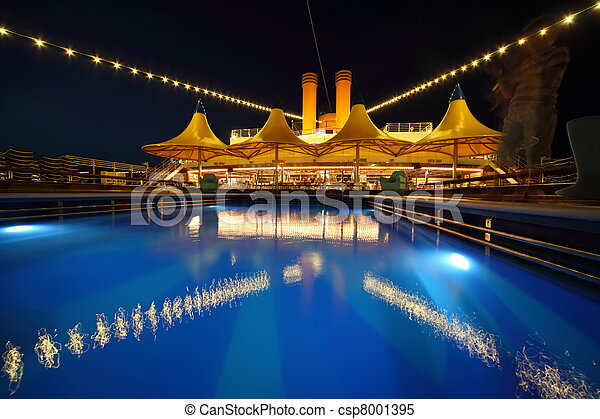 illuminated deck of ship at evening. swimming pool in deck of ship - csp8001395