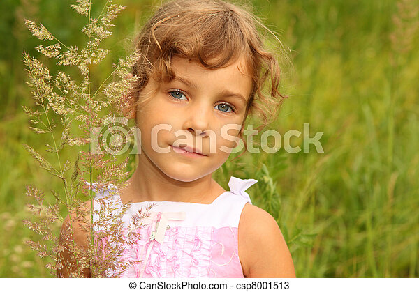 beautiful little girl in pink dress stands in tall grass on nature - csp8001513