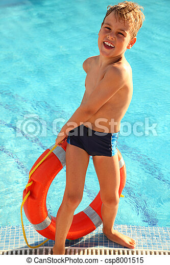 Cheerful little boy pulls out red buoy from the swimming-pool - csp8001515