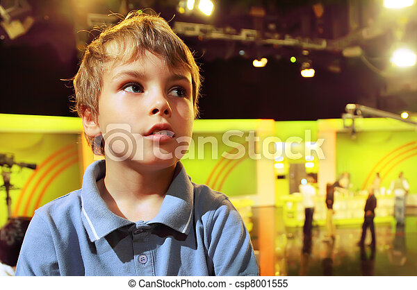 Little boy stands with folded hands in auditorium against the background of television broadcast - csp8001555