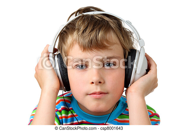 Little boy in striped shirt and in headphone puts hands on it and stares - csp8001643