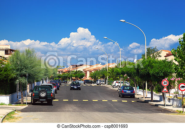 Cars drive on road and on the sidewalks are palm trees in residential area. - csp8001693