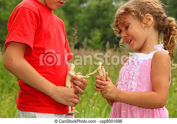 little brother and sister play with wooden little manikins in nature. manikins greet each other. focus on manikins. - csp8001696