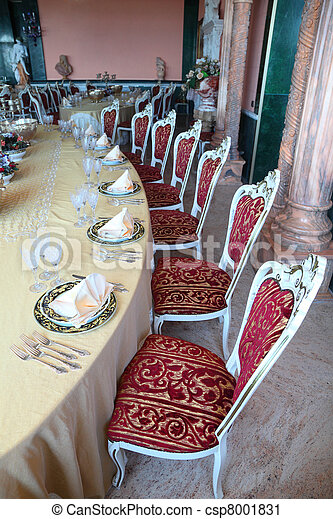Red chairs and big dinner table with empty dishes: plates with placemat, forks, knives and goblets - csp8001831