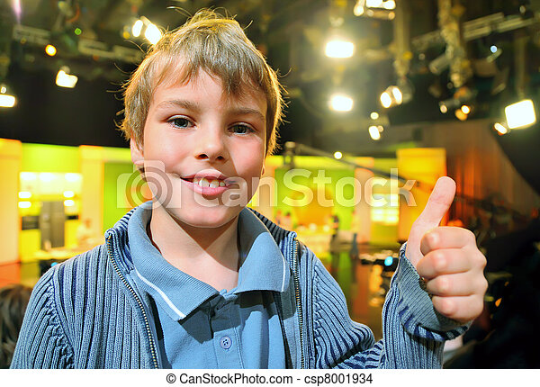 """Little smiling boy stands in auditorium and shows """"ok"""" against the background of television broadcast - csp8001934"""