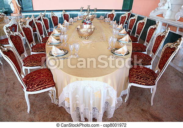 Big oval dinner table with candlestick, copper and empty dishes: plates with placemat, forks, knives and goblets - csp8001972