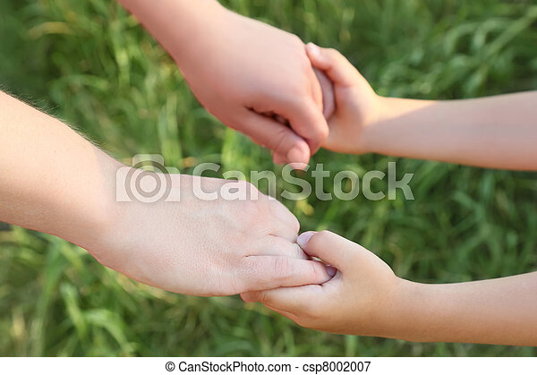 closeup of mother and son hands holding each other, green grass, horizontal - csp8002007