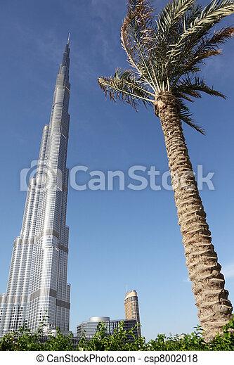 DUBAI - APRIL 17: Burj Dubai skyscraper, palm and plants in front, sunny day, 17 april 2010 in Dubai, UAE - csp8002018