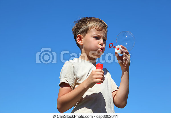 Boy stands straight and inflates soap bubbles in summer - csp8002041