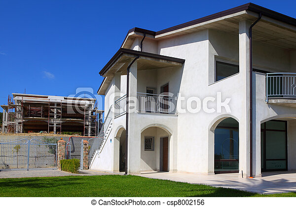 New finished white two-story house with garden, balcony and stairs to the right and unfinished building to the left - csp8002156
