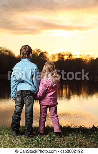 Little girl in pink clothes and boy in blue jacket standing back on bank of river and admire on sunset - csp8002192
