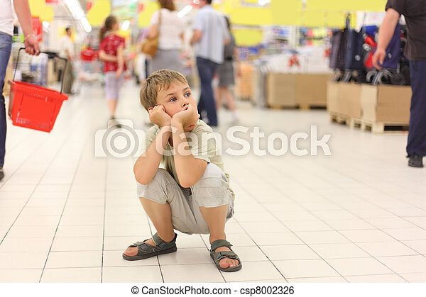 little boy sitting alone on hunkers in big store, chin on hands, looking at side - csp8002326