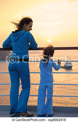 beautiful woman and her daughter both wearing tracksuits are standing on deck of ship and looking at setting sun. ship in out of focus. - csp8002418