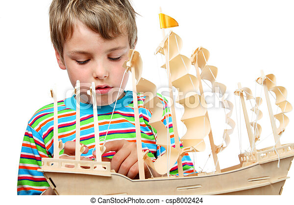 Small boy in striped shirt work with zeal on artificial ship, he fixes sails - csp8002424