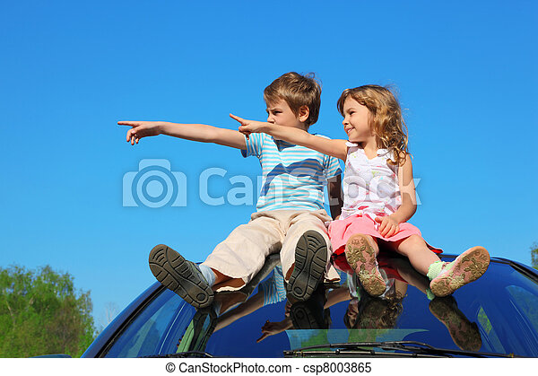 little boy and girl sitting on car roof on blue sky, looking to left side and showing by finger - csp8003865